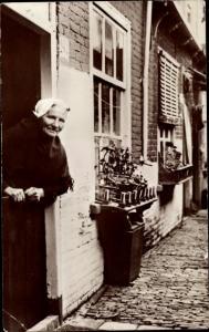 Ak Scheveningen Den Haag Südholland, Dame an ihrem Wohnhaus