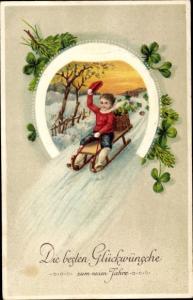 Ak Glückwunsch Neujahr, Kind auf Schlitten, Hufeisen, Kleeblätter