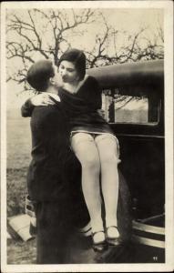 Foto Ak Mann hebt Frau vom Autoreifen, hochgerutschter Rock, Strümpfe, Beine
