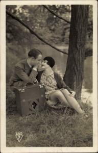 Ak Frau mit hochgerutschtem Rock und Mann auf einer Wiese, Kofferradio, Strümpfe