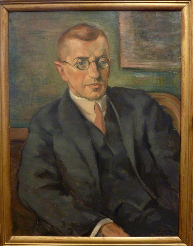 Kock, Mack. Bildnis eines jüngeren Herrn mit Brille, im Anzug. Öl auf Malpappe. Unten rechts signiert u. datiert: 'Kock 28'.