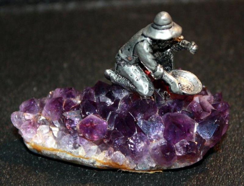 Kleine Amethyststufe mit Goldsucher Dat. 1981 und undeutlich Signiert, Metallguss, kniende miniaturhafte Gestalt beim Go