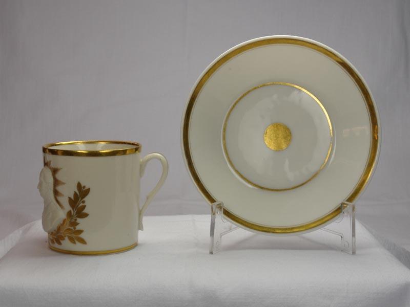Tasse und Untertasse, deutsch, um 1815-20, ungemarkt, im Stil von Sevres, zylindrische Form, verziert mit Halbportraits von Wellington und Blücher in Biskuitporzellan vor einer goldenen Sonne, umrandet von goldenen Lorbeerzweigen, bezeichnet