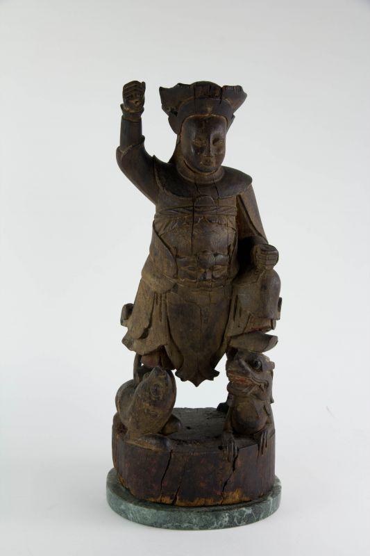 Figur, China, wohl Ming Dynastie (1368 bis 1644), Holz, geschnitzt, Tempelfigur, Wächter, auf Löwen und Drachen stehend, ursprünglich farblich gefasst und bemalt, schöne Ausarbeitung, Fehlstellen, auf modernen Steinsockel montiert. H: 43,5 cm