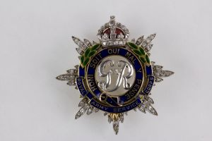 Regimentsabzeichen,  des Royal Army Service Corps, England, George VI, 2. Weltkrieg, Platin/Weißgold ? bekrönter Stern mit aufgesetzten kleinen Brillanten, in der Mitte die Initialen G VI R, umgeben vom Band des Hosenbandordens in Gold, blau emaillie...