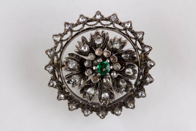 Brosche, Mitte 19. Jh., Gold mit Silber aufgelegt, verziert mit Brillanten in Altschliff, in Mitte grüner Stein, wohl später, 4 kleine Brillanten fehlen. D: 3 cm, Gewicht: 11 g