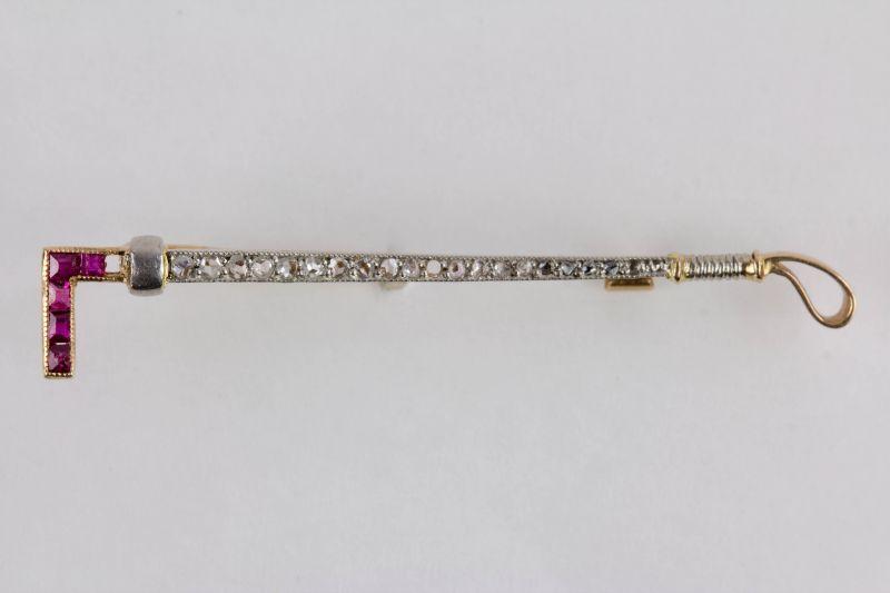 Anstecknadel,  Anf. 20. Jh., 585er Gold, undeutlich punziert, in Form eines Poloschlägers, besetzt mit Rubinen und kleinen Diamanten, ein Rubin, und zwei Diamanten fehlen, guter Zustand, ausgefallen.   L: 4,5 cm
