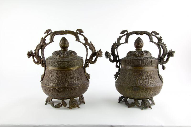 2 Deckelgefäße, Tibet, 19./20. Jh., Messing getrieben, verziert mit verschiedenen Heiligendarstellungen und Ornamenten, gegossene Griffe, als Drachen plastisch ausgearbeitet, wohl Körnerschalen für religiöse Zeremonien, ein Henkel locker, Gebrauchsspur...