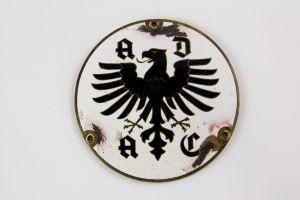 ADAC Plakette, wohl Weimarer Republik, an den Schraubstellen starke Ausplatzer, Rückseite: ADAC 4. Auflage Hauptverwaltung L-CHR-Lauer Nürnberg. D: 9 cm