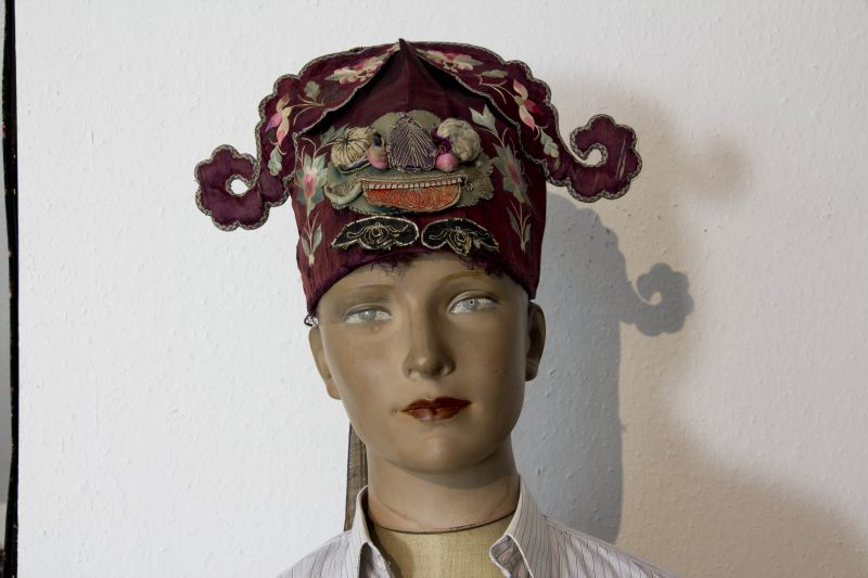 Kinder-Kopfbedeckung, China, um 1900, Ende Qing Dynastie, in Form eines Fo-Hundes, dunkelrote Seite bestickt mit Blumen und Fischen, aufgesetztes Gesicht mit herausgestreckter Zunge eines Fo-Hundes, teilweise stärkere Gebrauchsspuren, ein Zahn fehlt, S...