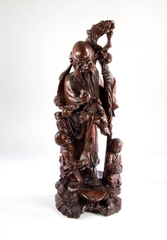 Figur, China, 20. Jh., geschnitzt, Rosenholz, Shoulao, Gott der Langlebigkeit mit Drachenstab und 2 Kindern, feine Schnitzerei, Augen aus Bein eingesetzt, Trockenrisse, guter Zustand. H: 54 cm