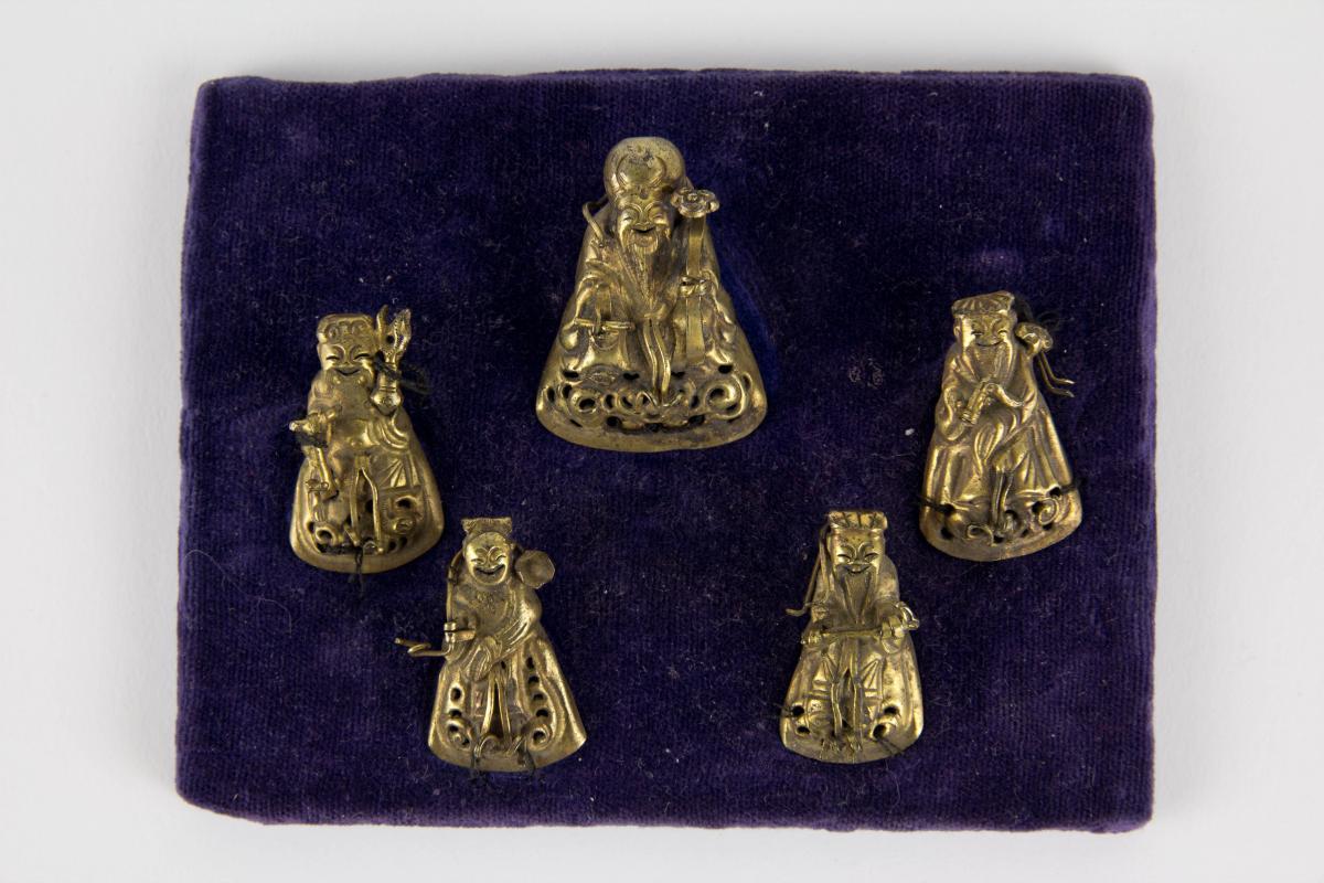 Glücksgötter, China, um 1900, Glücksgötter für Mützen, wohl Silber, vergoldet, auf Samtkissen genäht, Gebrauchsspuren. H: 3,5 cm bis 4 cm