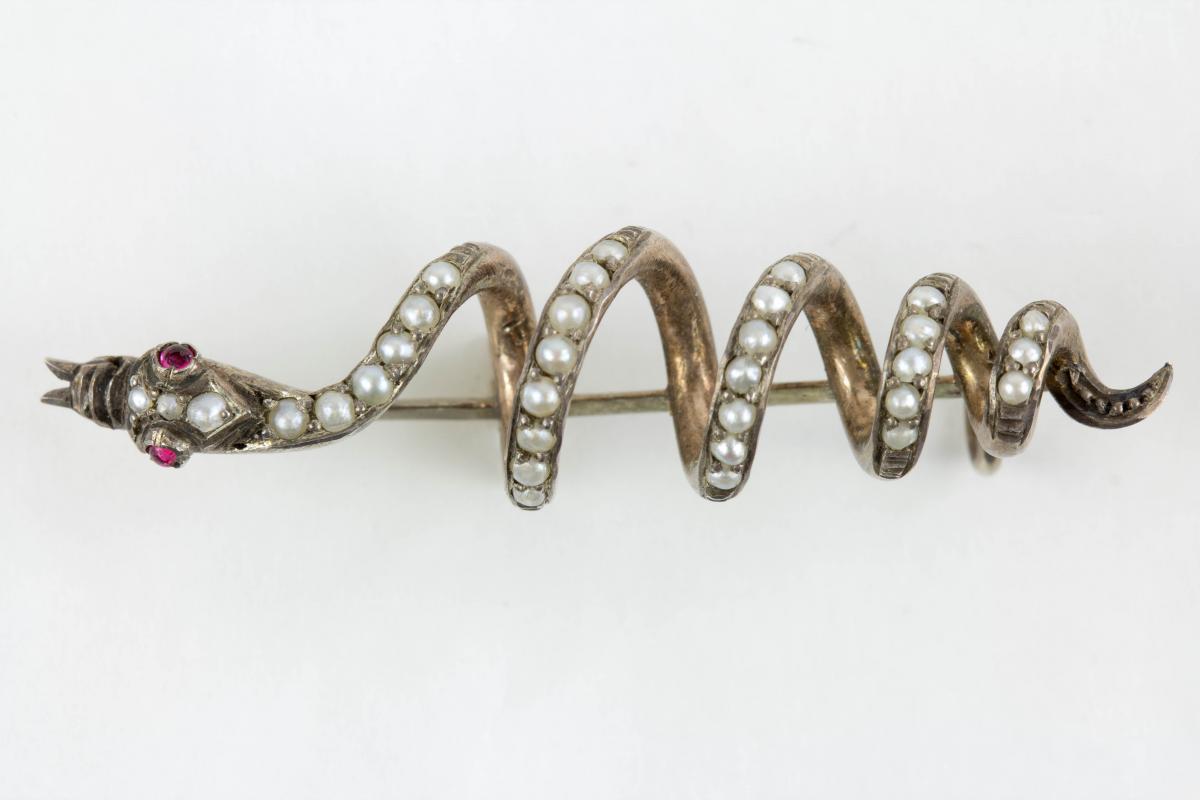 Brosche, 19. Jh., Silber, nicht gestempelt, in Form einer Schlange, mit Flussperlen und zwei Rubinen besetzt, sehr dekorativ, Gebrauchsspuren. L: 4,5 cm