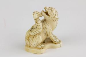 Netsuke, Japan, Meiji-Zeit, Bein, Tiger, geschnitzt und geschwärzt, signiert. H. 3,5 cm.