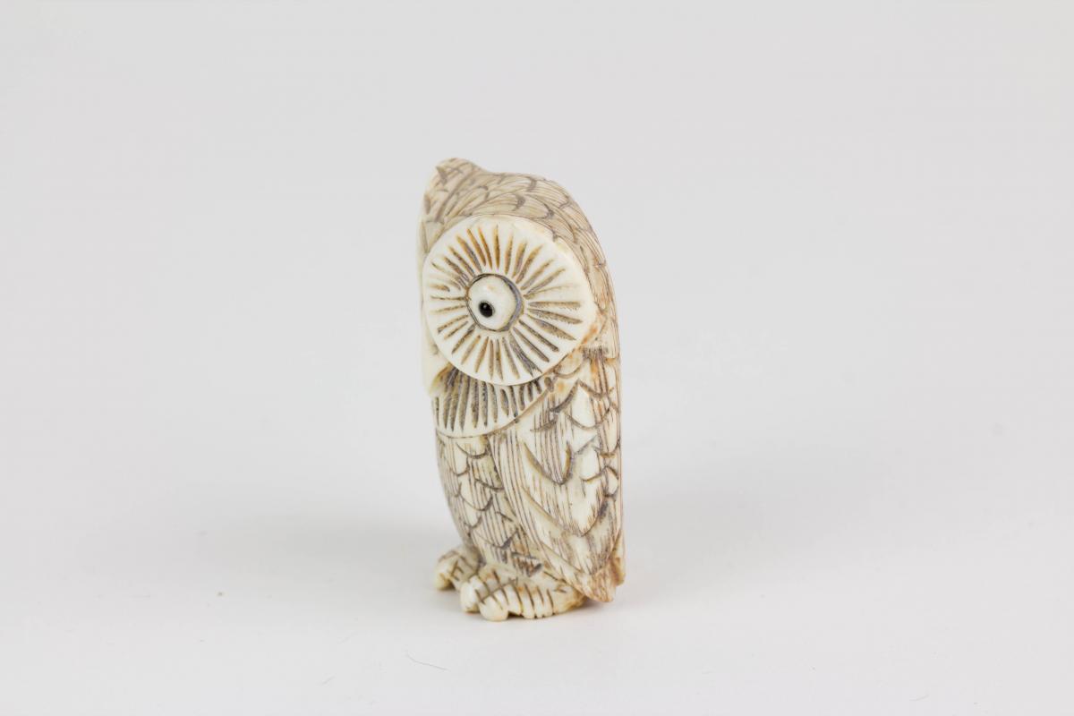 Netsuke, Japan, Anf. 20. Jh., Bein, Eule, schwarz abgesetzt, signiert, Gebrauchsspuren, H: 4 cm. 1