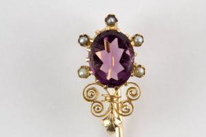 Krawattennadel, um 1870, 585er Gold, ungemarkt, mittig Amethyst, flankiert von kleinen Perlen, Amethyst auf der rechten Seite mit kleinen Chip, schöne Juwelierarbeit. L: 7 cm.