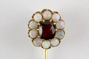 Krawattennadel, Ende 19. Jh., Gold, gemarkt Fuchs 4, mittig geschliffener Granat, flankiert von kleinen Opalen, schöne Juwelierarbeit. L: 7 cm.
