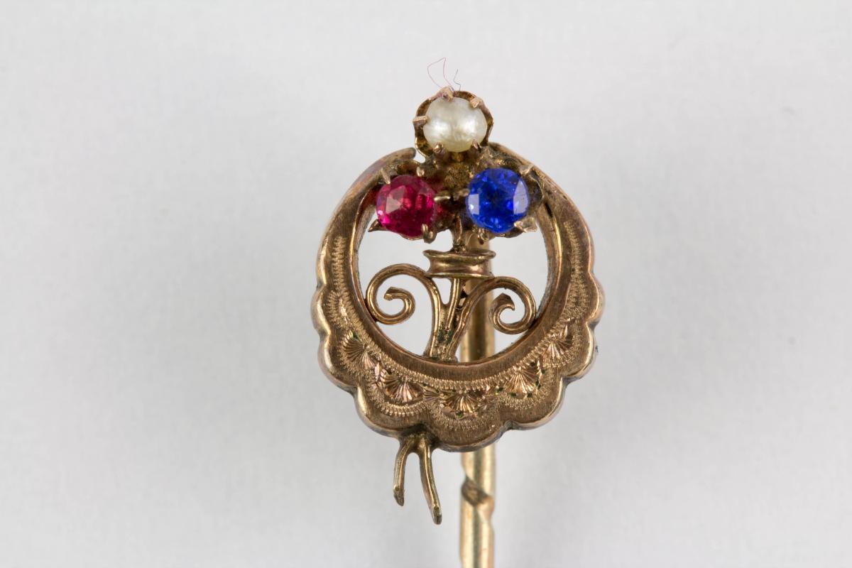Krawattennadel, Ende 19. Jh., 585er Gold, und Silber, ungemarkt, halbmondförmig, graviert mittig Kleeblatt, mit Rubin, Perle und Saphir besetzt. L: 6 cm. 0
