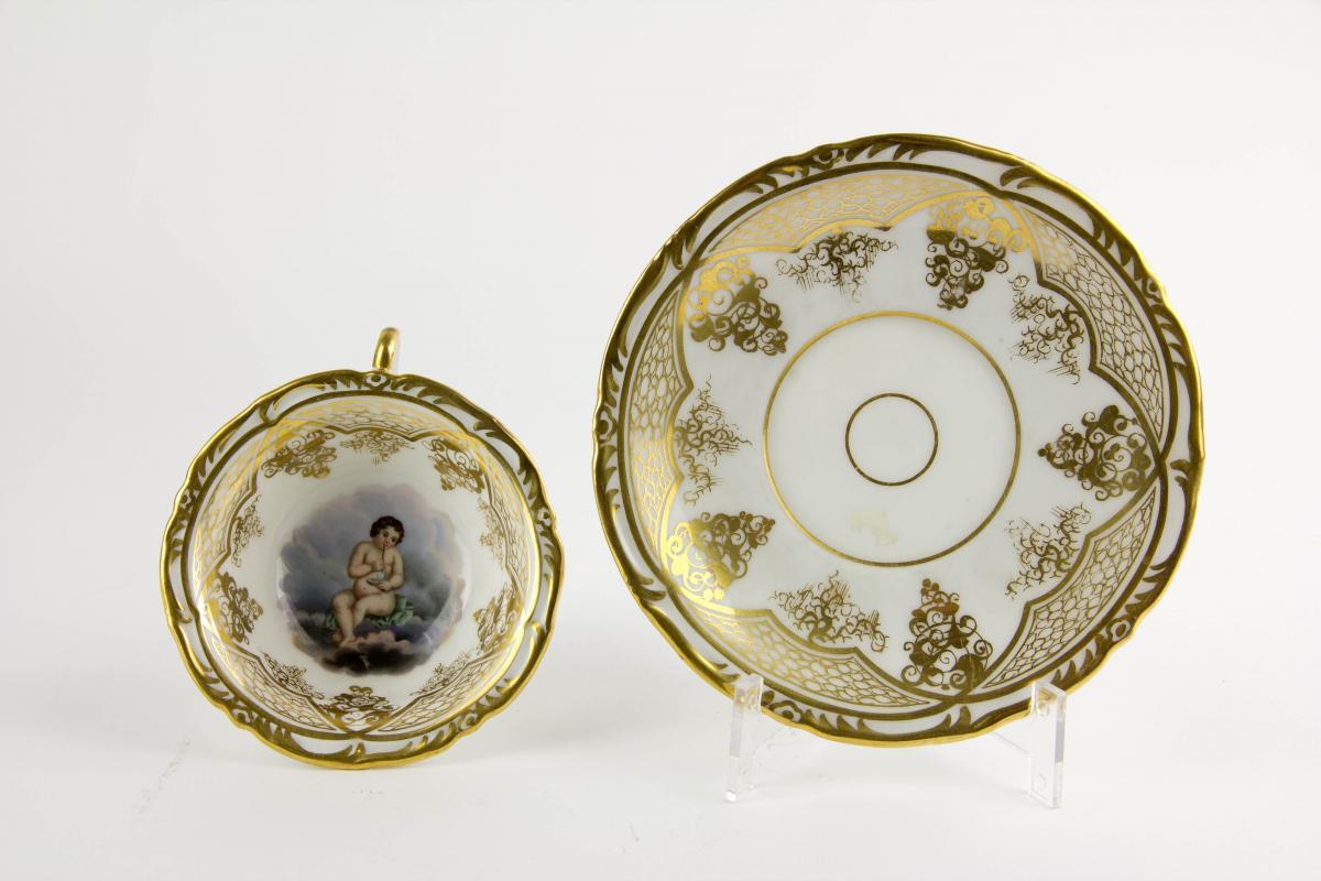 Tasse und Untertasse, Schlesien, Mitte 19. Jh., Gold- und Blumenmalerei, auf Tassengrund Darstellung eines pfeiferauchenden Puttos auf Wolke. H: 6 cm. 0