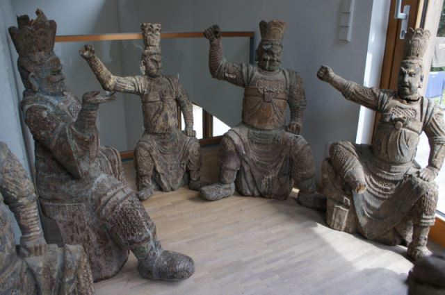 Gruppe von 8 großen Tempelwächtern aus Holz. China nach Art der Ming-Dynastie. Mit Resten von alten Farbpigmenten und diversen Beschädigungen an Extremitäten. Sehr dekorativ, als Gruppe von 8 Figuren sehr selten. 1