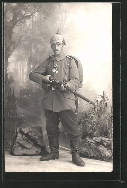 Foto-AK Portrait deutscher Infanterist in Uniform mit Pickelhaube, Gewehr 88 und Orden EK II