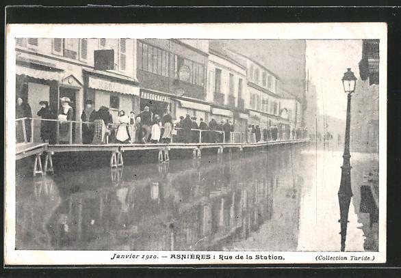 AK Asnières, Rue de la Station, Janvier 1910, Leute laufen über Stege, Hochwasser
