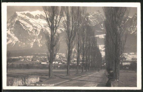 AK Maienfeld, Strassenpartie mit lesendem Mann und Blick nach den Bergen