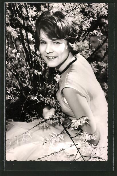AK Schauspielerin Petra Himboldt kniet neben einem Blühenden Busch