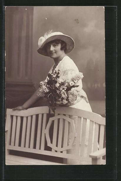 AK Dame mit Hut hält einen Blumenstrauss im Arm