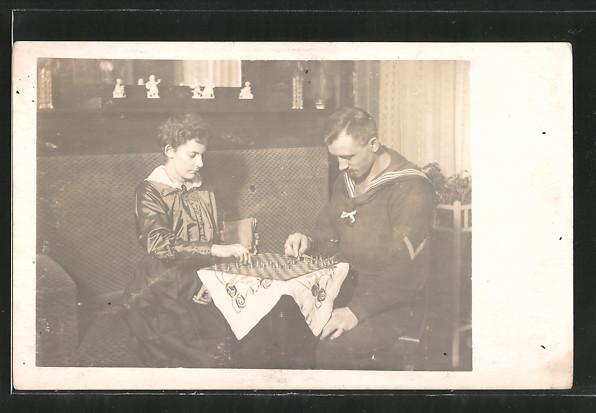 Foto-AK Matrose in Uniform mit seiner Frau beim Halma-Spiel