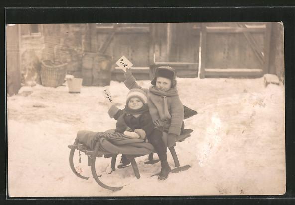 Foto-AK zwei kleine Kinder sitzen auf einem Schlitten