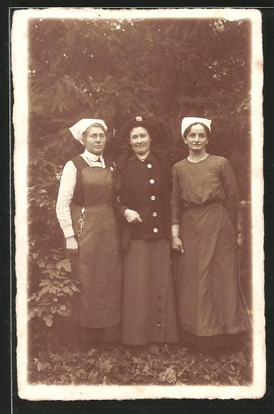 Foto-AK Dame, Arm in Arm mit zwei Frauen mit weisser Haube