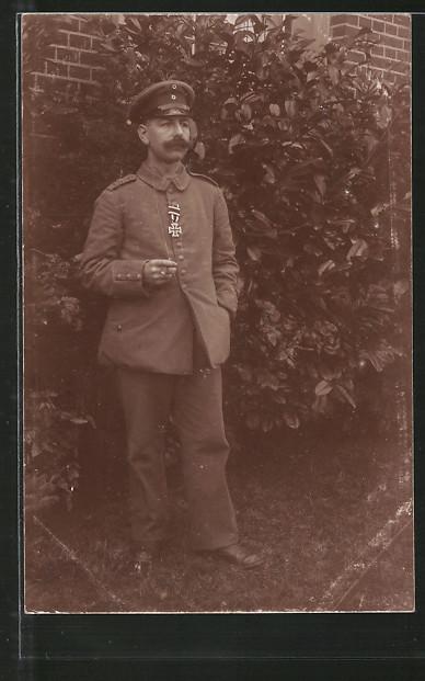 Foto-AK Feldgrauer mit EK II in Garten