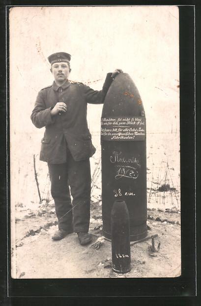 Foto-AK Soldat steht neben einer 38 cm und einer 12 cm Granate
