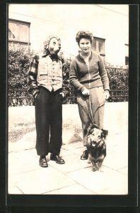 Foto-AK Mann mit Mecki-Maske steht neben einer Dame mit Hund