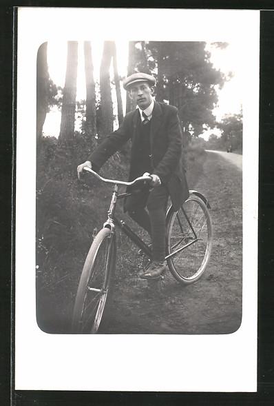 Foto-AK Junger Mann mit Schiebermütze auf Fahrrad