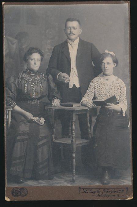 Fotografie H. Bogler Frankfurt, Portrait eines Paares mit Tochter, Vater mit Zigarre, Tochter mit Buch, Mutter mit Rosen