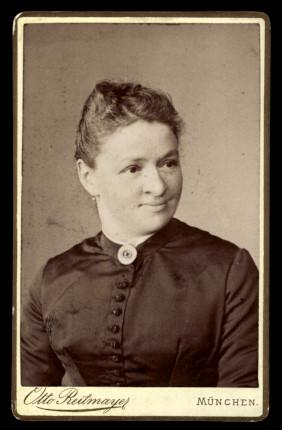 Fotografie Otto Reitmayer München, Portrait Frau im schwarzen Kleid mit Brosche