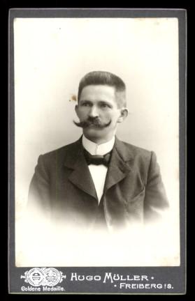 Fotografie Hugo Müller Freiberg, Portrait Mann mit Schnurrbart trägt Anzug und Fliege