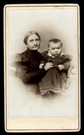 Fotografie J. Hecht Dedeleben, Portrait alte Dame im schwarzen Kleid hält Baby im Arm