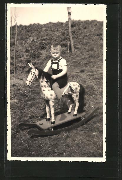 Foto-AK Knabe auf Schaukelpferd auf Wiese