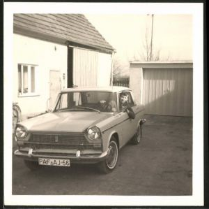 Fotografie Auto Fiat, Knabe sitzt in Limousine, PKW vor einer Garage