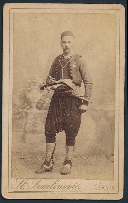 Fotografie St. Tomlinovic, Cernik, Portrait Mann in Tracht mit Pistolen & Dolch, rückseitig überstempelt Mostar