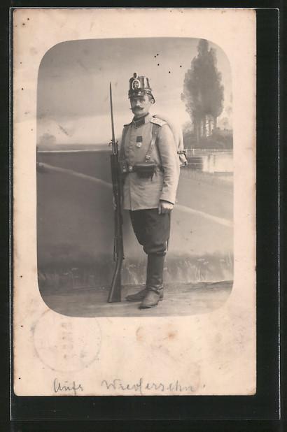 Foto-AK Landsturmmann mit Tschako, aufgepflanztem Bajonett und Orden