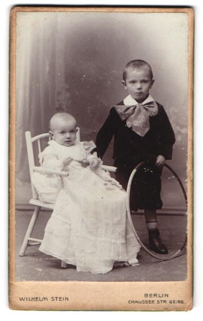 Fotografie Wilhelm Stein, Berlin, Portrait Knabe mit Holzreifen und Säugling in Taufkleid