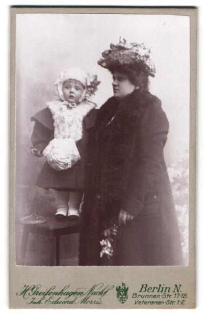 Fotografie H. Greifenhagen Nachf., Berlin-N, Portrait Mutter mit Tochter in Winterkleidung
