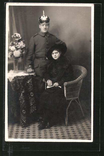Foto-AK Feldgrauer mit Pickelhaube und junge Dame in schwarz