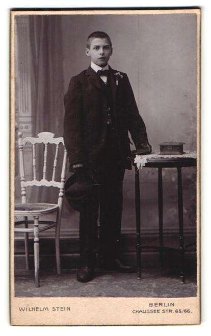 Fotografie Wilhelm Stein, Berlin, Portrait Knabe in schwarz mit Handschuhen und Hut