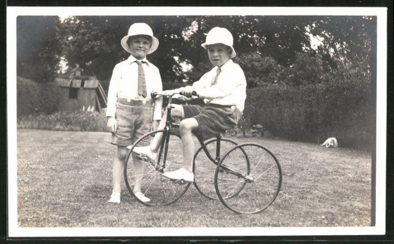 Fotografie Fahrrad, Knaben spielen mit Dreirad im Garten