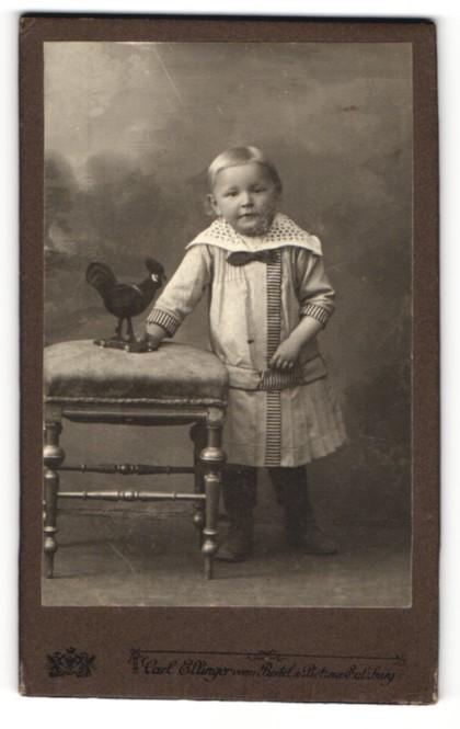 Fotografie Carl Ellinger, Salzburg, Portrait Kleinkind mit Spielzeughahn